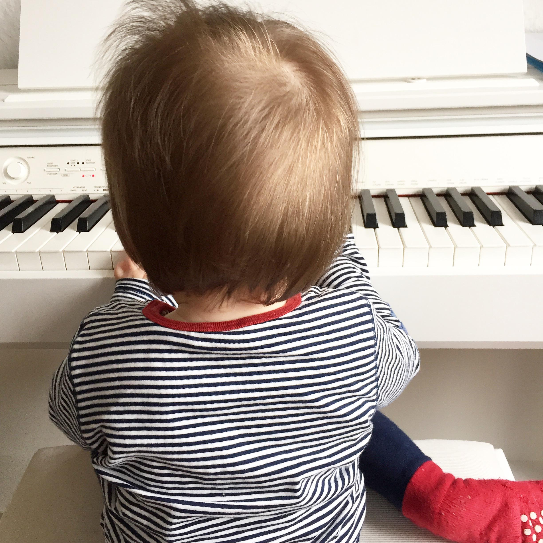 Kind sitzt am Klavier