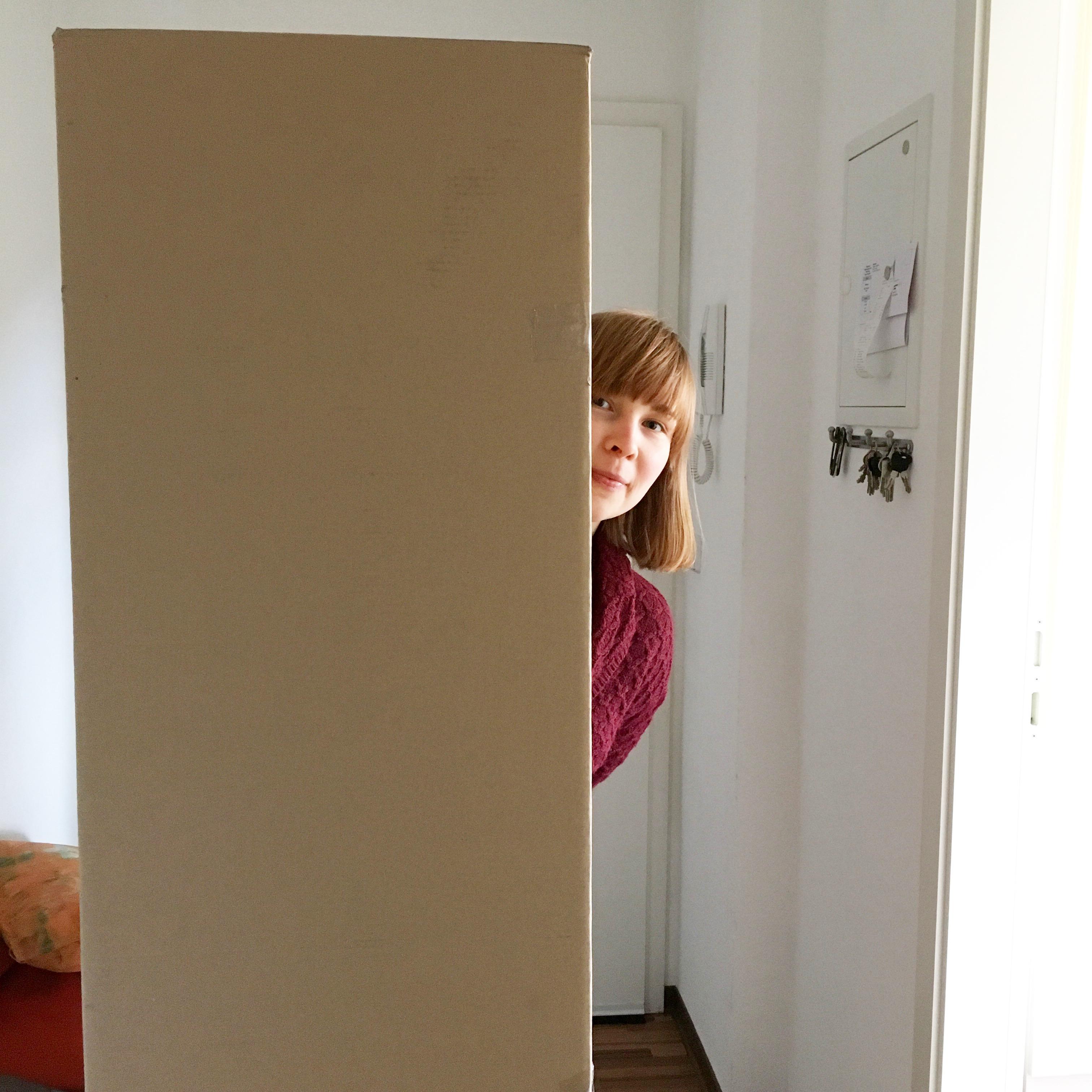 Frau lukt hinter Karton hervor
