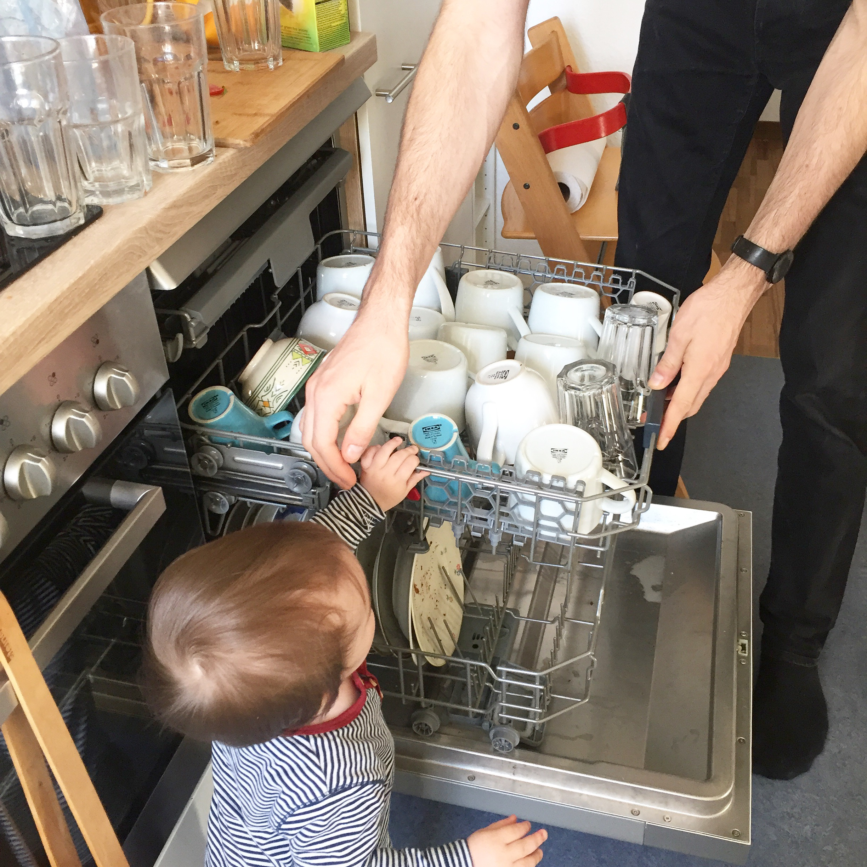Papa und Kind räumen Geschirrspüler aus