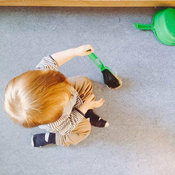 Kind mit Handfeger